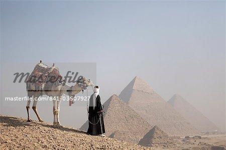 Un guide bédouin avec son chameau, avec vue sur les pyramides de Gizeh, patrimoine mondial de l'UNESCO, le Caire, Egypte, Afrique du Nord, Afrique