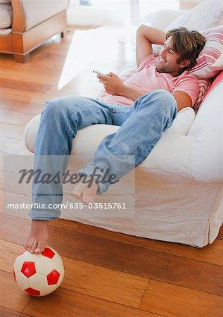 Homme couché sur le canapé à regarder la télévision