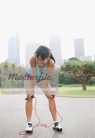 Femme au repos après l'exercice avec la corde à sauter