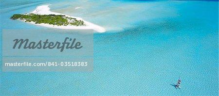 Catamaran sailing near a desert island, the Maldives, Indian Ocean
