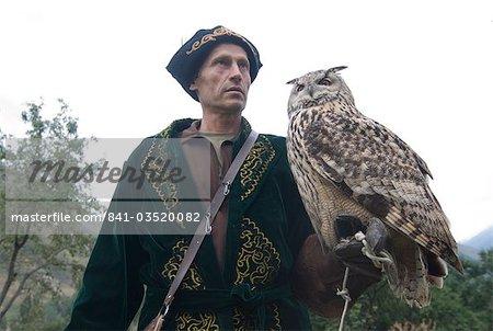 Kyrgyz eagle hunter with a rock eagle-owl (Bubo bengalensis), Sunkar Eagle Farm, Kazakhstan, Central Asia, Asia