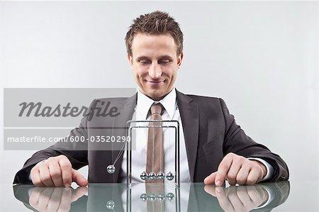 Businessman With Newton's Cradle