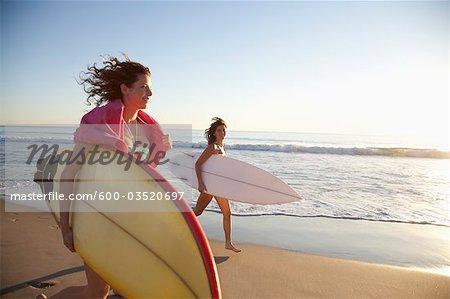 Young Women Running on Beach Holding Surf Boards, Zuma Beach, California, USA