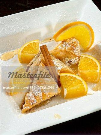 Baklava mit Puderzucker, Orange, Honig und Zimt