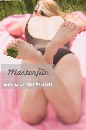 Femme prélasser avec des feuilles de trèfle entre ses orteils