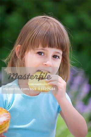Fille mange une pomme beignet