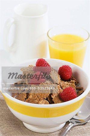 Cereal flakes with milk and raspberries, orange juice