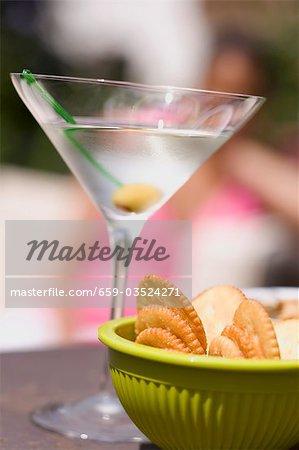 Martini avec vert olive, craquelins, femme en arrière-plan