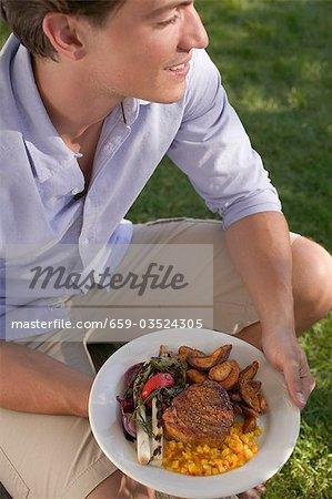 Jeune homme tenant une assiette de steak grillé & accompagnements