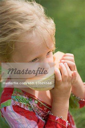Petite fille mangeant une tranche de melon