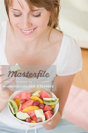 Femme manger coin de pomme de salade de fruits
