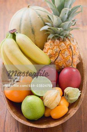 Fruits exotiques et agrumes dans un bol en bois