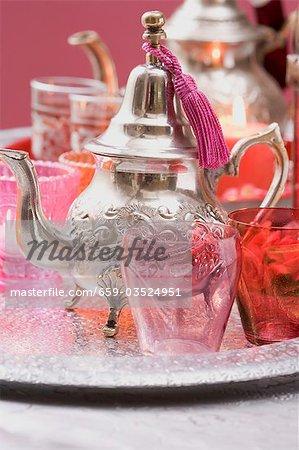 Silberne Teekanne, Gläser und Windlichter auf Tablett