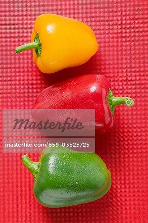 Différents poivrons colorés avec des gouttes d'eau sur fond rouge