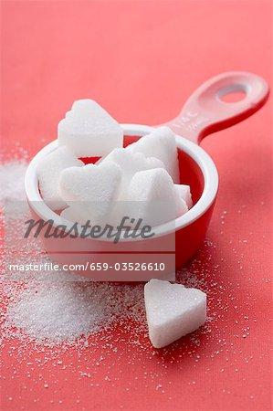 Morceaux de sucre en forme de coeur en rouge tasse à mesurer