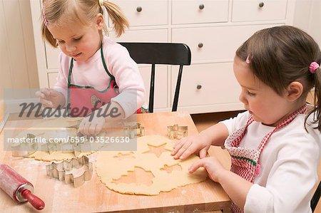 Zwei kleine Mädchen Kekse Ausschneiden