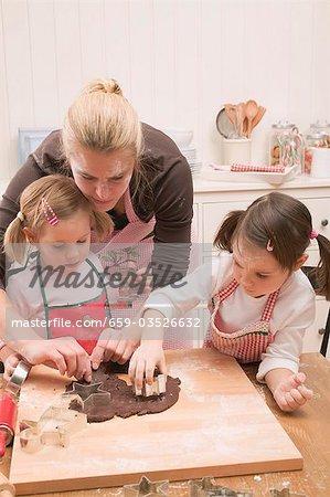 Frau und zwei kleine Mädchen Ausschneiden Schokoladenkekse