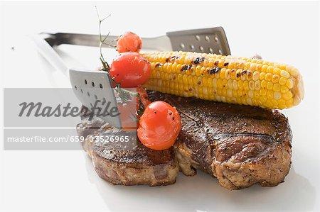 Bifteck d'aloyau grillé, maïs en épi, tomates, grill pinces