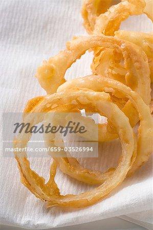 Frittierte Zwiebelringe auf Küchenpapier (Nahaufnahme)