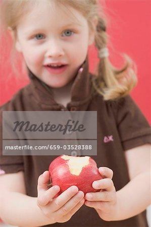 Petite fille tenant une pomme mangée en partie