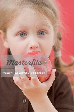 Petite fille de mordre dans la pomme