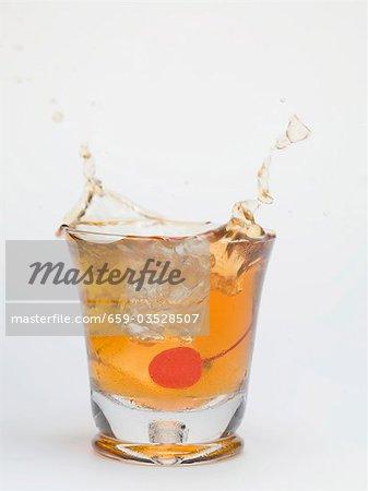 Eiswürfel in ein Glas Manhattan fallen