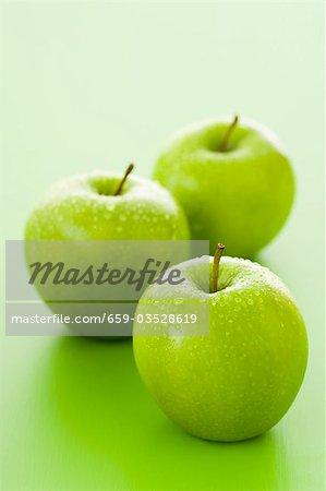 Trois pommes Granny Smith avec gouttes d'eau