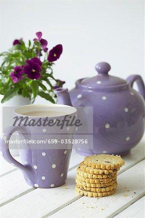 Teapot, mug of tea, fruit shortcakes and pansies
