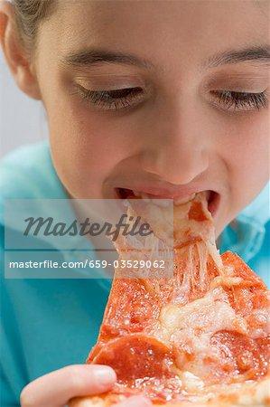 Petite fille mangeant pointe de pizza