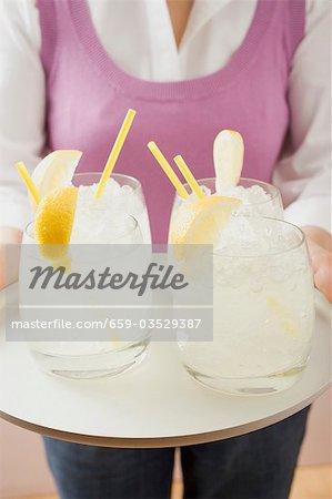 Frau hält Fach Gläser gefüllt mit Limonade