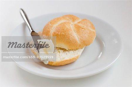Brötchen mit Butter und Messer auf Platte