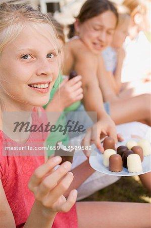 Filles mangent les guimauves enrobées de chocolat à l'extérieur