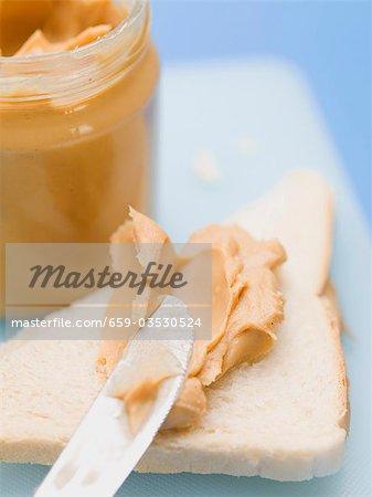 Beurre d'arachide sur du pain blanc et dans le récipient