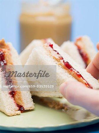 Hand Griff nach Erdnussbutter und Gelee sandwich