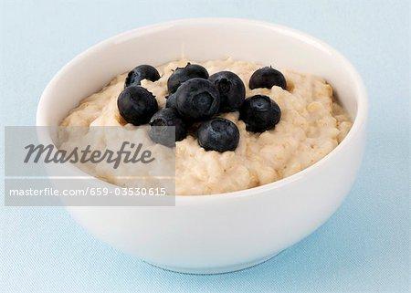 A bowl of porridge with fresh blueberries