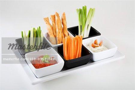 Tablett mit Gemüsesticks, pikante Strohhalme und dips