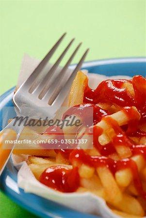 Fourche située à côté de frites avec du ketchup
