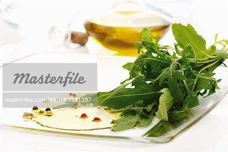 Fresh rocket on chopping board, olive oil