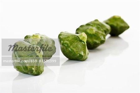 Several green patty pan squashes