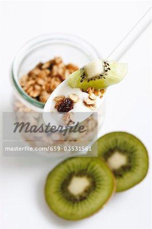 Joghurt mit Müsli und Kiwi Frucht auf Löffel