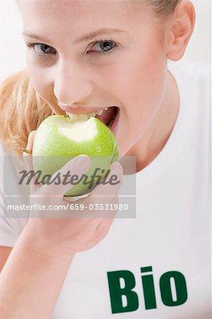 Woman eating organic green apple