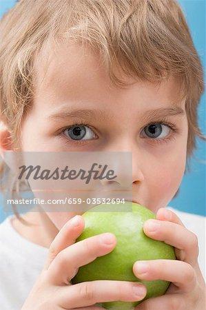 Petit garçon mordre dans une pomme