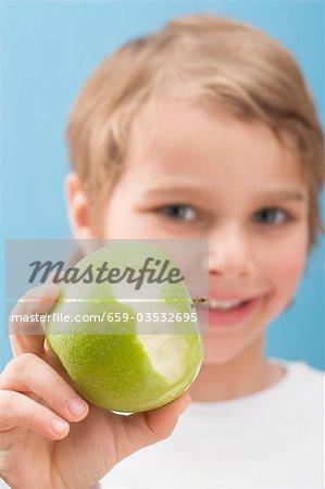 Petit garçon tenant une pomme mangée en partie