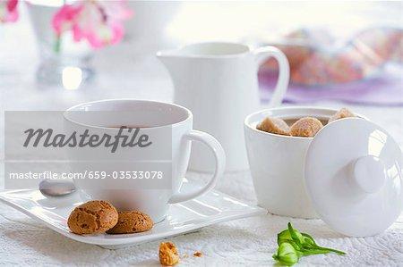 Eine Tasse Tee mit Zuckerdose, Milchkännchen und Gebäck