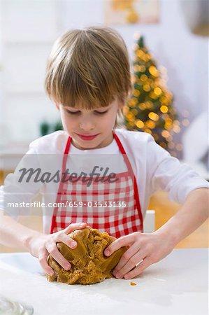 Kleiner Junge kneten Teig für weihnachtsgebäck