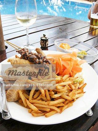 Plaque d'aliments cuits sur le barbecue et les jetons à la table de piscine