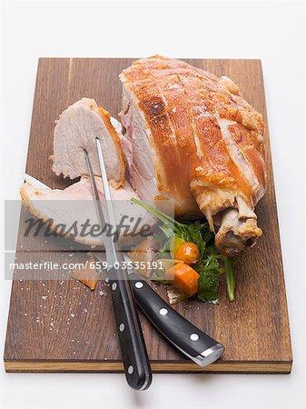 Roast pork on wooden board