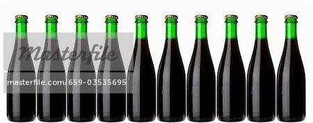 Zehn grüne Flaschen stehend in einer Zeile (stämmig, dunkles Bier)