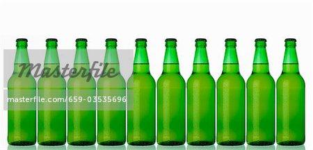 Zehn grüne Flaschen stehend in einer Zeile (Lager)