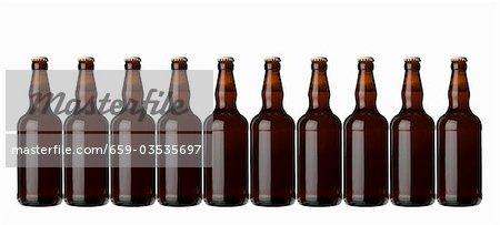 Zehn braune Flaschen stehend in einer Zeile (Lager)
